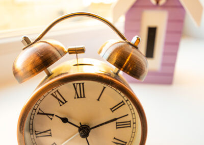 Photograph of alarm clock with lilac coloured beach hut ornament in the background