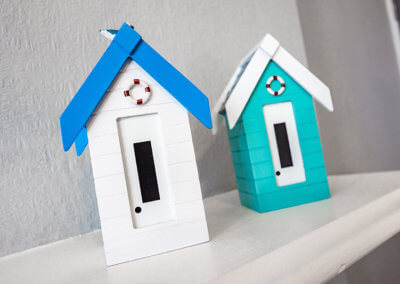 Photograph of two beach hut ornaments, one white, one teal, on a white pained mantlepiece