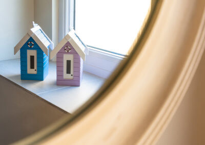 Photograph of beach hut ornaments relected in edge of circular mirror