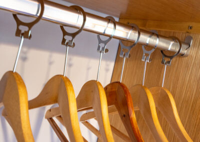 Photographs of wooden coat hangers on silver rail