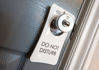 Photograph of Do Not Disturb sign hanging on a nickel finish door handle