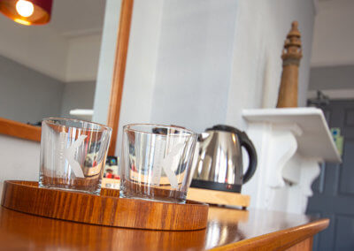Photograph of branded glasses on wooden tray with complimentary tea, coffee and kettle, period fireplace mantlepiece in the backgound