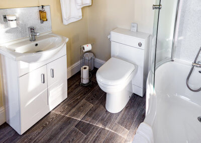 Photograph of room 1 bathroom with white suite, chrome fittings and wood laminate flooring