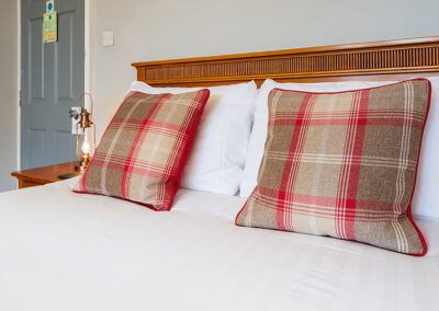 Photograph of the bed in room 1 with white linen, tartan cushions and latern side light