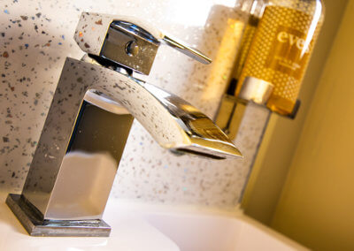 Close up photograph of chrome mixer tap and handwash dispenser