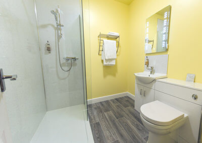 Photograph of Room 6 ensuite showeroom with large walk in shower and glass screens, chrome towel rail, illuminated mirror and white built-in sink and toilet
