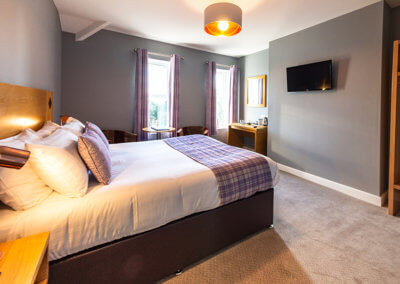 Photograph of room 6 looking towards bed with purple tartan soft furnishings, occasional chairs with table, desk and wall mounted flat screen TV