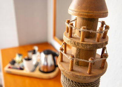 Close up photograph of an ornamental wooden lighthouse with tea and coffee making facilities in the background