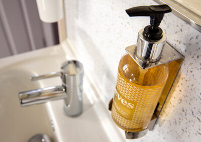 Photograph of the complimentary handwash in wall mounted dispenser above white sink and chrome mixer tap