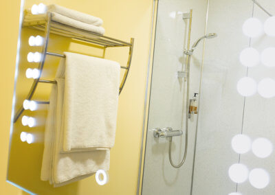 Photograph of a chrome towel rail, white towels and shower cubicle reflected in an illuminated mirror
