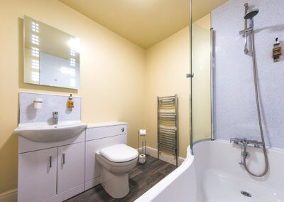 Photograph of the en-suite bathroom with white suite, pale yellow walls and wood effect vinyl flooring