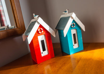 Photograph of two ornamental beach huts on wooden chest of drawers. One beach hut is red, the other one is blue and both have a seagull sitting on the roof.